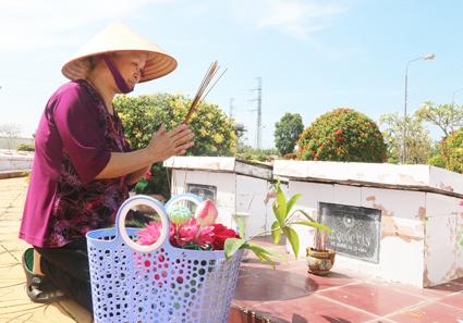Bà Loan viếng mộ con trai ở Nghĩa trang Liệt sĩ quận Ô Môn. Ảnh: DUY KHÔI