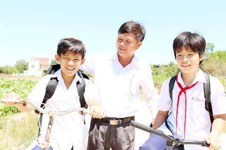 Trưởng ấp Nguyễn Văn Ngoan (đứng giữa) và các học sinh trên con đường nội đồng Phú Tân - Võ Dõng.