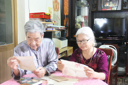 Ông bà An Ninh bồi hồi bên kỷ vật con trai- Liệt sĩ Lê Văn. Ảnh: DUY KHÔI