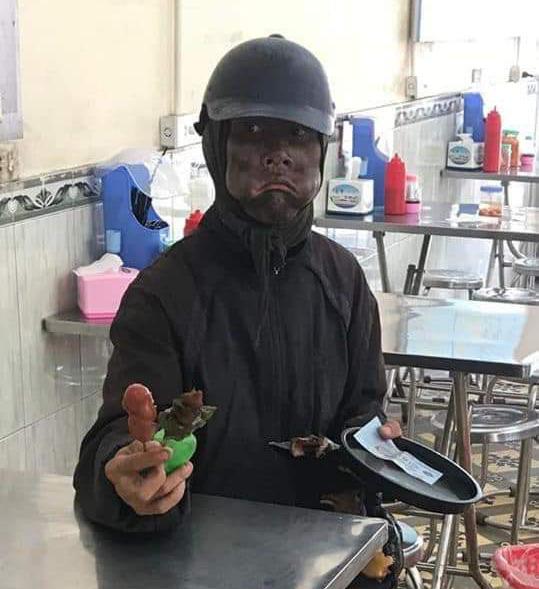 Người đàn ông bôi đen mặt, phùng má, tay cầm đầu gà đi lang thang xin tiền - Ảnh 1.