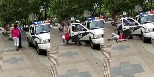 Trung Quốc: Cảnh sát quật ngã người phụ nữ đang đang bế trẻ - Ảnh 1.