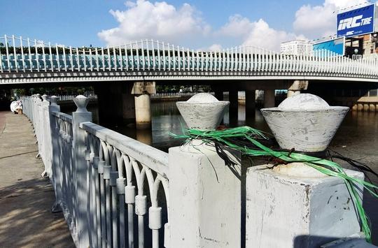 Người dân dùng dây kẽm buộc tạm bợ lan can bị tháo hết ốc vít.