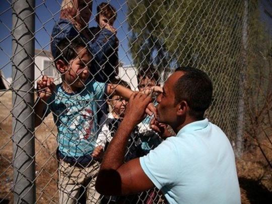 Cảm động nụ hôn qua hàng rào của ông bố tị nạn người Syria - Ảnh 2.