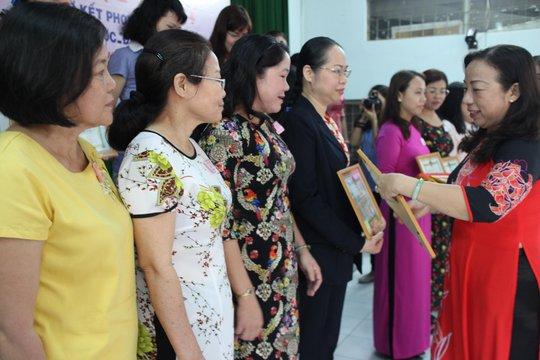 Bà Võ Thị Minh Phượng, Phó Ban Nữ công LĐLĐ TP HCM, trao giấy khen cho nữ CNVC-LĐ đạt thành tích 2 giỏi