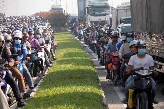 Làn đường xe máy kẹt cứng, nhiều người liều mình lưu thông qua làn ô tô, cắt đầu xe container, xe tải mà tìm đường thoát.