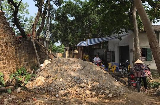 Đống đất to chắn gần hết một con đường làng
