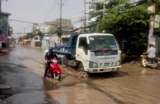 Con đường nước ngập giữa nắng thiêu ở TP HCM - Ảnh 1.