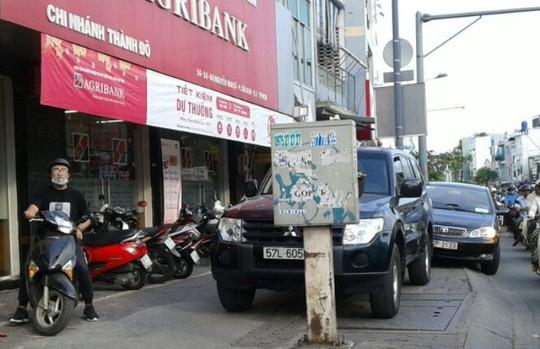 Xe ô tô đậu trên vỉa hè trước một quán cà phê buộc người đi bộ phải đi ngay dưới đường