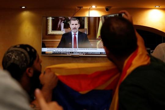 Người dân theo dõi phát biểu của Vua Tây Ban Nha Felipe VI tại Barcelona. Ảnh: Reuters