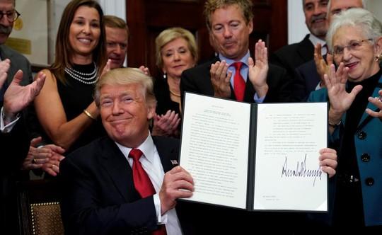 Ông Donald Trump ký sắc lệnh làm suy yếu Obamacare. Ảnh: Reuters
