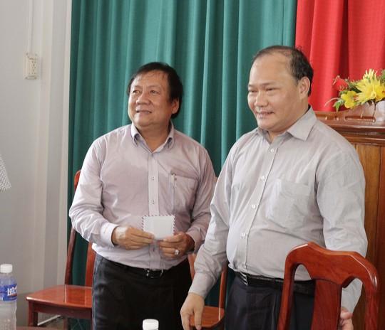Thứ trưởng Hoàng Văn Thắng (phải) tặng quà cho người dân vùng sạt lở ở Vàm Nao. Ảnh: LÂM LONG HỒ