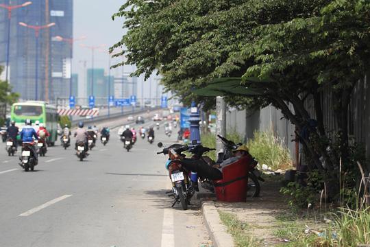 Thời tiết trên xa lộ Hà Nội khá nóng khiến các bác tài xe ôm mệt lã mưu sinh