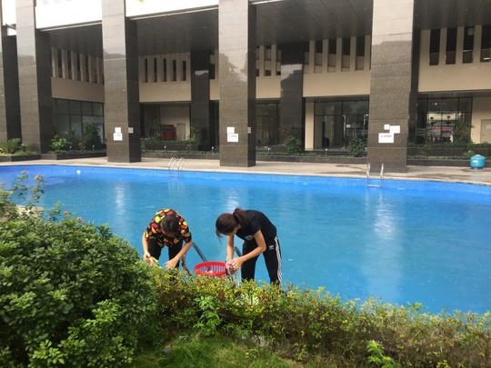 Thiếu nước sạch do nhiễm dầu, người dân Hà Nội phải giặt quần áo ở bể bơi - Ảnh 1.
