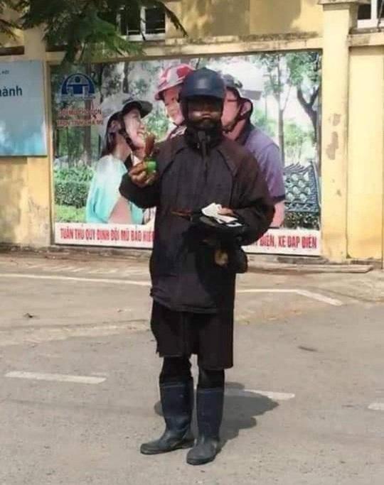 Người đàn ông bôi đen mặt, phùng má, tay cầm đầu gà đi lang thang xin tiền - Ảnh 2.