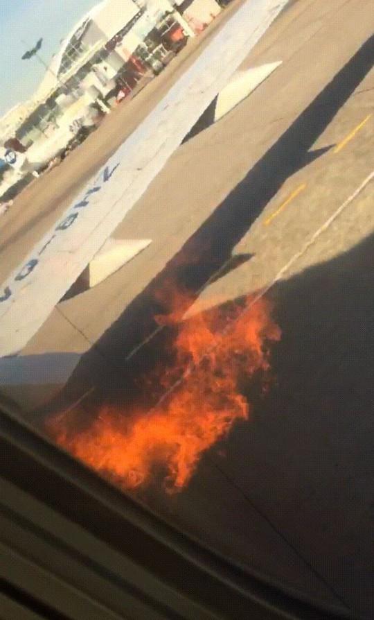 Động cơ cháy, hành khách mở cửa nhảy lên cánh máy bay thoát thân - Ảnh 1.