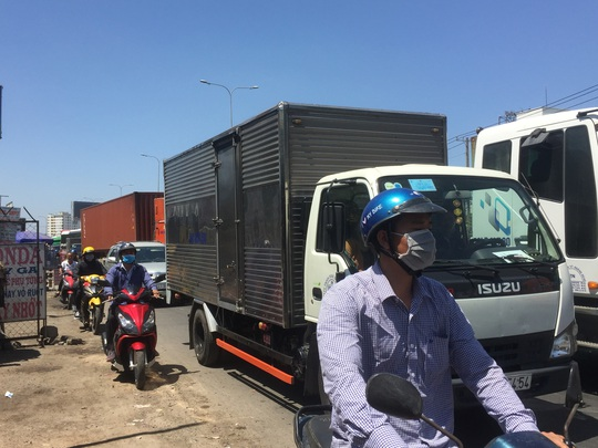 Xe tải tông dải phân cách, văng qua làn đường xe máy gần cầu vượt Sóng Thần - Ảnh 2.