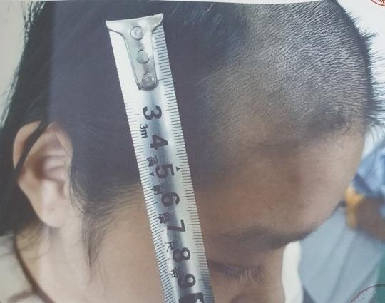Bố trói tay con vào gậy ghì xuống nền nhà hành hạ, cắt trọc tóc - Ảnh 2.