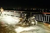 Đang đi dừng lại múa may rồi châm lửa đốt xe máy trên cầu