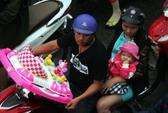 Trẻ nhỏ mệt mỏi cùng bố mẹ vượt mưa trở về thành phố