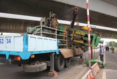 Xe tải chở cồng kềnh vướng cầu vượt, cả cỗ máy rớt xuống đường