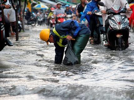 """Người dân TP HCM """"bì bõm"""" sau cơn mưa lớn"""