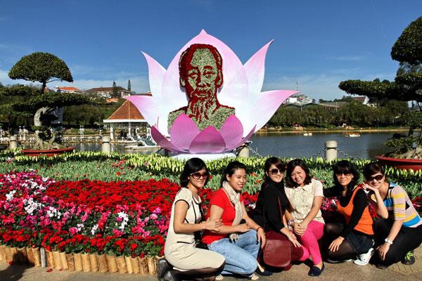 Du khách chụp hình lưu niệm trước tượng Bác Hồ làm bằng hoa