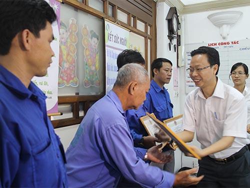Ông Nguyễn Thành Đô - Phó Chủ tịch LĐLĐ quận 1, TP HCM - khen thưởng các tài xế xe ôm bắt cướp