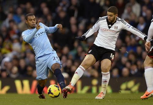 Fernandinho (trái) tranh bóng với Aden Taarabt của Fulham