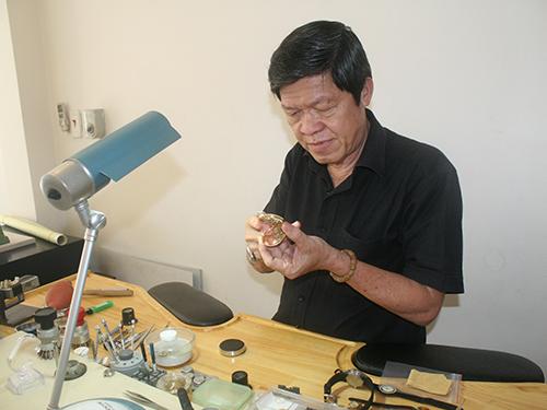 Ông Quách Cao thẩm định giá trị một chiếc đồng hồ cổ