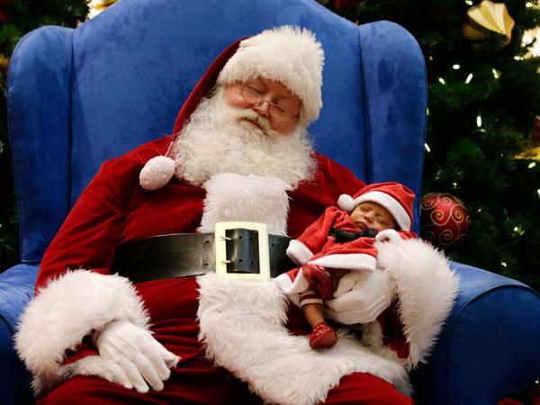Ông già Noel dỗ giấc ngủ cho em bé 4 tuần tuổi Leilani Mejico ở trung tâm mua sắm bang California. Ảnh: AP