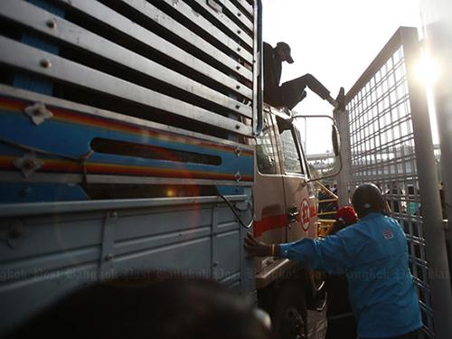 """Người biểu tình cho xe tải """"mở đường"""" vào sân vận động Thái-Nhật ngày 25-12 Ảnh: THE BANGKOK POST"""