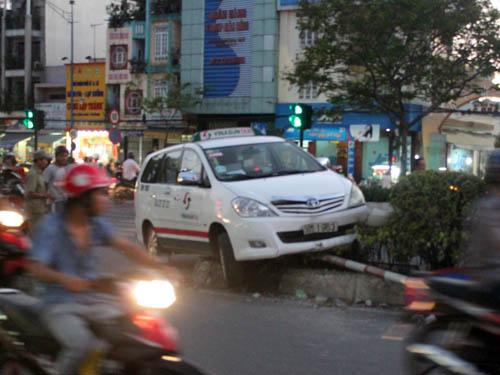 """Do né xe máy vượt đèn đỏ băng ngang đường khiến xe taxi phải """"ngồi"""" trên dải phân cách."""
