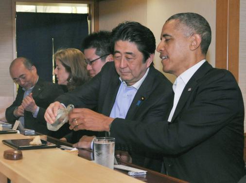 Lảnh đạo hai nước Mỹ - Nhật vui vẻ ăn uống tại một nhà hàng sushi. Ảnh: Reuters