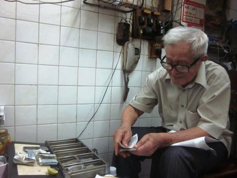 90 tuổi, ông Phồn vẫn minh mẫn ngồi thu và trả tiền dư cho khách mỗi ngày. Ảnh: Thi Hà.
