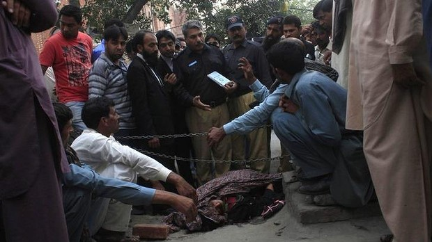 Police collect evidence near the body of Farzana Iqbal, who was killed by family members outside  Lahore High Court for marrying the man she loved.