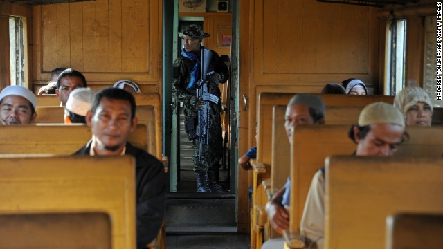 A Thai soldier stands guard as passengers travel in a train on the southern line to the border town of Sungai Kolok, May 30, 2014