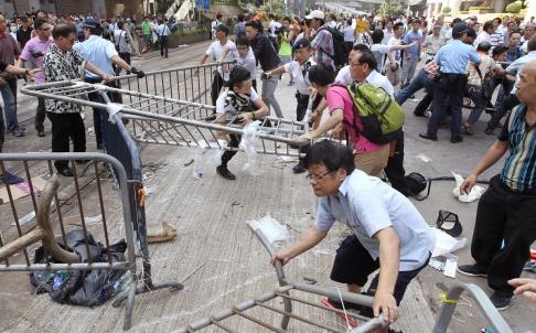Người biểu tình dựng rào chắn và đụng độ với nhóm phản đối phong trào Chiếm lĩnh trung tâm ngày 13-10. Ảnh: SCMP