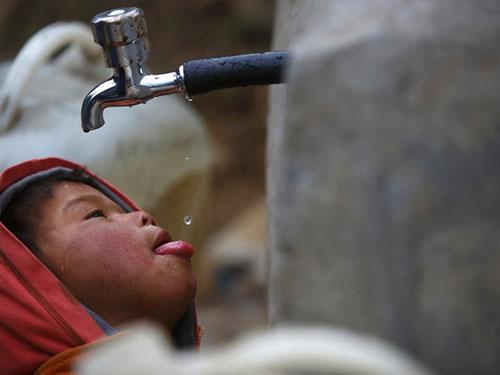 Một bé trai uống từng giọt nước ở vòi nước công cộng tại Nepal Ảnh: REUTERS
