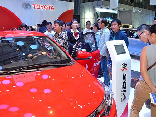 Giá ô tô Việt Nam quá cao so với các nước trong khu vực là do sản lượng quá nhỏ, đẩy chi phí sản xuất lên cao.  Trong ảnh: Khách hàng xem một mẫu xe ở Triển lãm Ô tô Việt Nam 2014 Ảnh: TẤN THẠNH