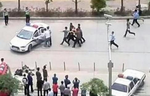 Nghi phạm bị áp giải vào xe cảnh sát. Ảnh: SCMP