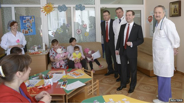 Russias Prime Minister Dmitry Medvedev (2nd R, front) visits a childrens hospital in the Crimean city of Simferopol, March 31, 2014