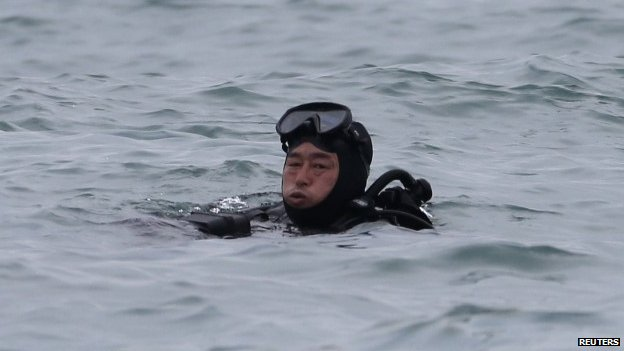 "A South Korean diver rests in the water during the rescue operation of the capsized passenger ship ""Sewol"", in the sea off Jindo April 18, 2014. A junior officer was steering the South Korean ferry when it capsized two days ago, investigators said on Friday, as rescuers battled strong tides and murky waters to search for hundreds of missing, many of them school children, feared trapped in the vessel"