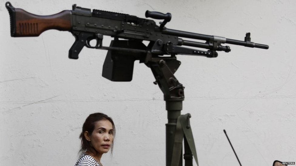 A morning commuter passes behind a machine gun mounted on a military vehicle (20 May 2014)