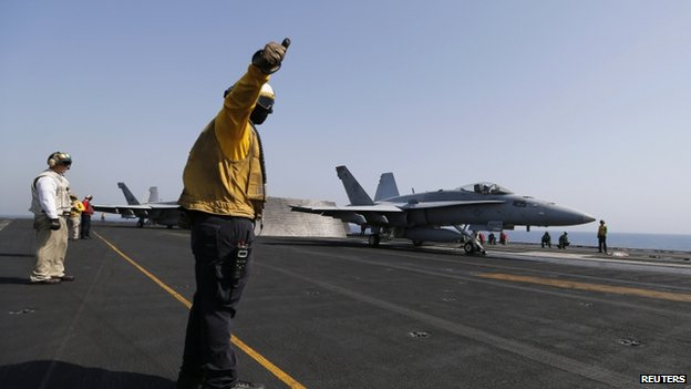 A F/A-18C Hornet takes off from an aircraft carrier