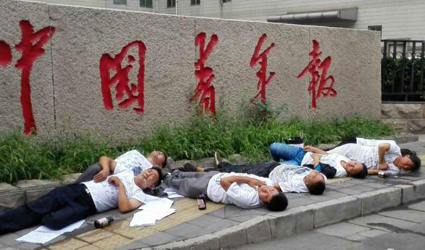 7 người nằm gục sau khi uống thuốc trừ sâu trước trụ sở báo China Youth Daily ở Bắc Kinh . Ảnh: CRI