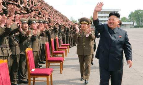North Korean leader Kim Jong-un waves during a photo session with soldier-builders in this undated photo released by North Koreas Korean Central News Agency