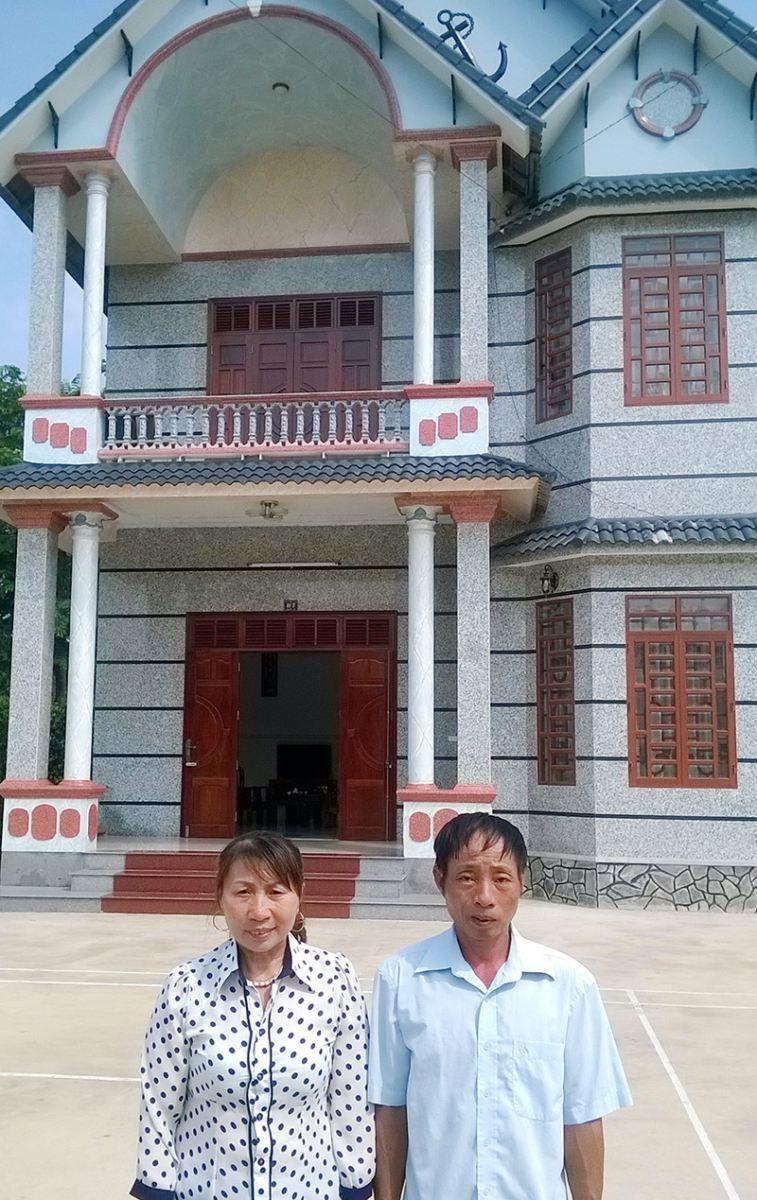 Vợ chồng ông Hoàng Thế - bà Hồ Thị Hoa trước ngôi nhà trị giá 2,5 tỉ đồng của gia đình