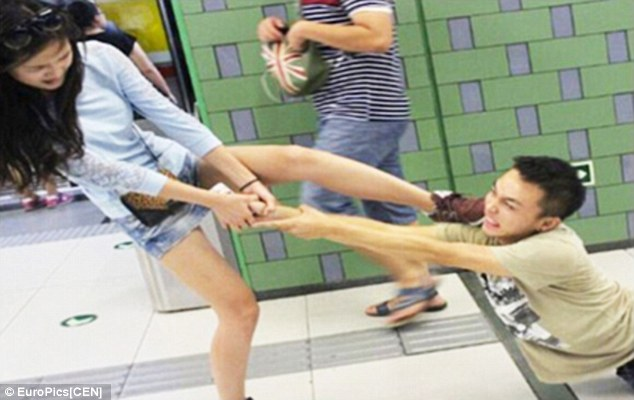 Fancy footwork: The frustrated woman uses her foot to try and free her boyfriends cellphone from his grasp, as they fight on the Beijing underground after he refuses to drop his iPhone