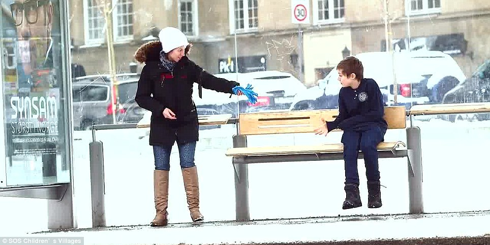 Gift: A woman gives Johannes her gloves. The stunt was to raise awareness of the plight of Syrian child refugees