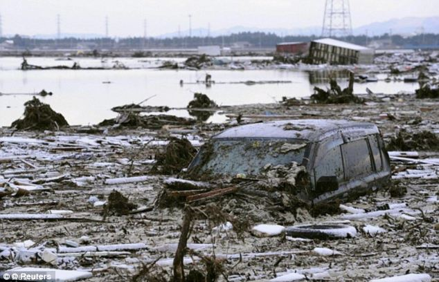 Wreckage: The earthquake sent the catastrophe tsunami hurling across the Pacific Ocean - wiping out entire communities, homes and families in the country. Above, a vehicle is covered in debris following the tsunami
